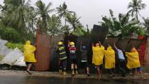 In this photo provided by the San Policarpo Firestation, firemen and police push up a steel fence as they clear roads during rain caused by Typhoon Surigae in the municipality of San Policarpo, Eastern Samar, eastern Philippines on Sunday April 18, 2021. An approaching typhoon has left at least one person dead, another missing and prompted the evacuation of more than 100,000 people as a precaution in the eastern and central Philippines, although the unusual summer storm is not expected to blow into land, officials said Monday. (FO1 Marianne Jabinal/ San Policarpo Firestation via AP)