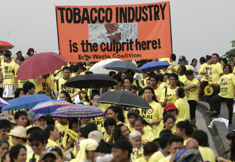 Protesters wearing yellow t-shirts display a streamer as they march towards the Philippine International Convention Center where ProTobEx, a large international tobacco fair is held, in suburban Pasay City south of Manila Thursday, March 15, 2012. Anti-smoking advocates have picketed the tobacco fair in the Philippines that has emerged as a battleground for the industry.  (AP Photo/Pat Roque)