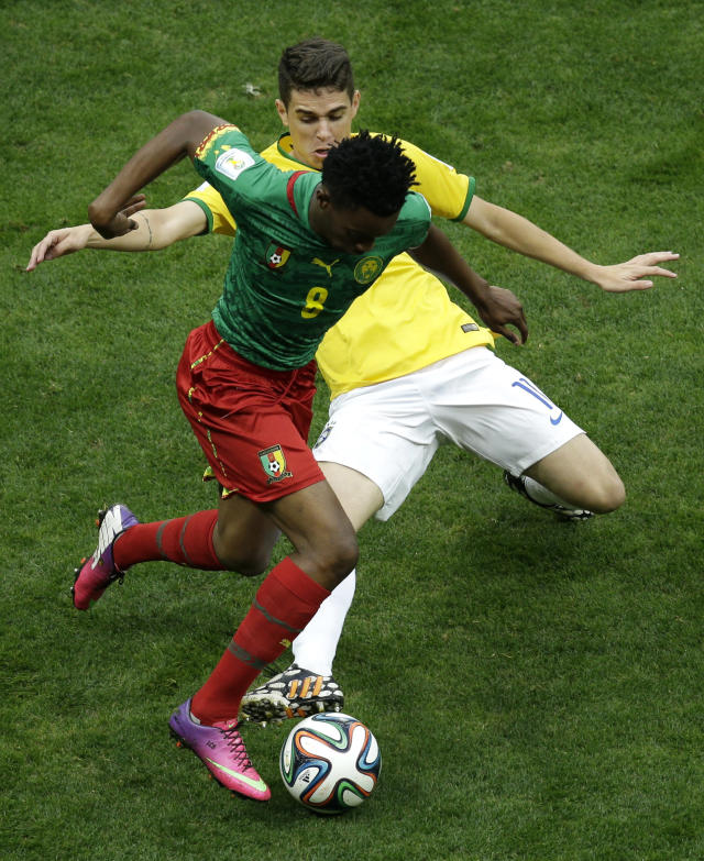 Brazil's Oscar fights for the ball with Cameroon's Benjamin Moukandjo during the group A World Cup soccer match between Cameroon and Brazil at the Estadio Nacional in Brasilia, Brazil, Monday, June 23, 2014. (AP Photo/Christophe Ena)