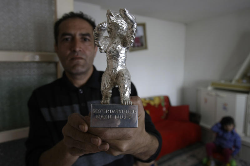 Nazif Mujic, the Gypsy scrap metal collector shows his award - the Silver Bear for best actor of the 63rd Berlin Film Festival at his home in the village of Poljice, 150 kms northeast of Sarajevo, on Wednesday, April 10, 2013. People in the Gypsy village of Poljice say they will never forget the night they almost fell off their chairs two months ago. Did they really hear the elegant woman on TV correctly? Could she really be talking about their neighbor, the toothless man who passed his days selling scrap metal and lived in the shack down the road? The camera switched to a frightened-looking Najif Mujic. Yes it was him. THEIR Nazif _ who had just left Matt Damon and Jude Law in the dust to win the best actor award at the Berlin Film Festival. (AP Photo/Amel Emric)