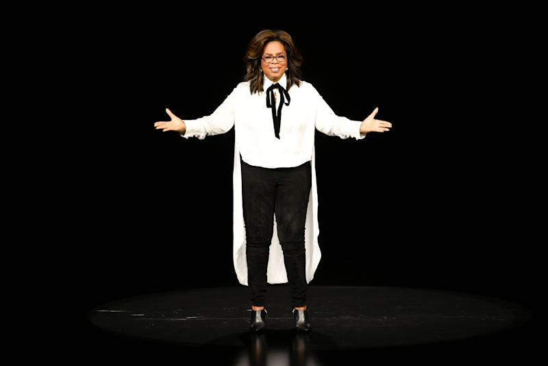 Oprah Winfrey looks breath-taking in white and black outfit in a talk show stage with her arms spread apart as she addresses the crowd.