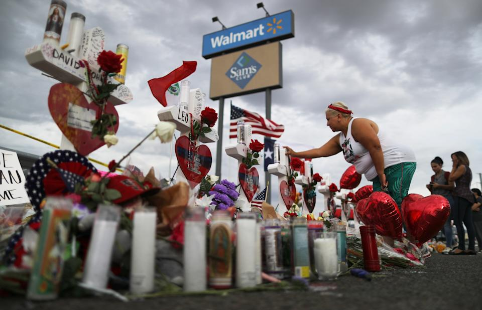 A woman touches a cross at a makeshift memorial for victims outside Walmart, near the scene of a mass shooting in El Paso, Texas. (Mario Tama/Getty Images)