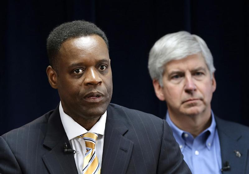 FILE - In this March 14, 2013 file photo, Kevyn Orr, Detroit's state-appointed emergency manager, speaks at a news conference in Detroit as Michigan Gov. Rick Snyder listens. In a report released late Sunday, May 12, 2013, Orr said Detroit is broke and faces a bleak future given the precarious financial path it's on. It was his first report on Detroit's finances since taking the job in March. (AP Photo/Paul Sancya, File)
