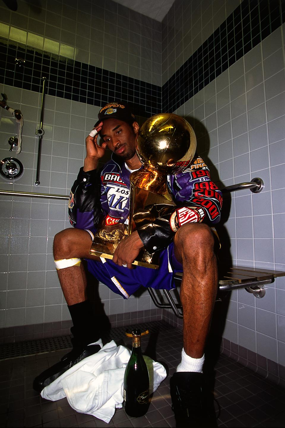 After the Lakers defeated the Philadelphia 76ers in five games to win back-to-back championships in 2001, Kobe Bryant enjoyed a quieter moment with the Larry O'Brien Trophy and a bottle of champagne in the locker-room showers. (Robert Mora/NBAE via Getty Images)