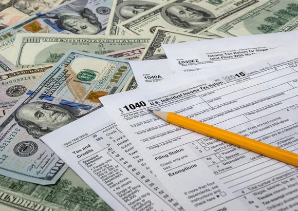 Tax forms with a pencil, laying on top of money.