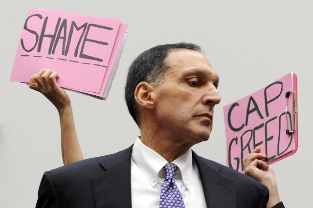 Protesters hold signs behind Richard Fuld, former Chairman and Chief Executive of Lehman Brothers Holdings, on Capitol Hill in Washington, October 6, 2008. REUTERS/Jonathan Ernst