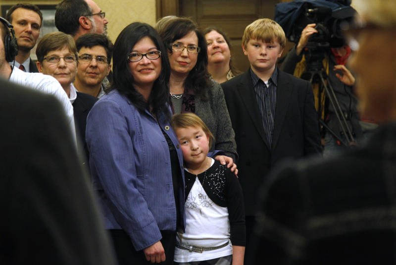 Heather Kawmoto, center left, and her partner Kay Lancaster stand with their daughter, Kayleigh Kawmoto, 9, during a signing ceremony for Referendum 74, a citizen-passed measure that legalizes same-sex marriage, Wednesday, Dec. 5, 2012, in Olympia, Wash. Gay couples can marry beginning Dec. 9. Kawmoto and Lancaster are planning to wed that day. (AP Photo/Elaine Thompson)