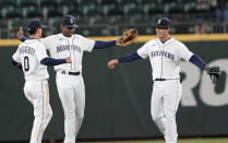 Seattle Mariners' Kyle Lewis, center, celebrates with teammates Sam Haggerty (0), and Dylan Moore, right, after the Mariners beat the Baltimore Orioles 5-2 in a baseball game, Tuesday, May 4, 2021, in Seattle. (AP Photo/Ted S. Warren)