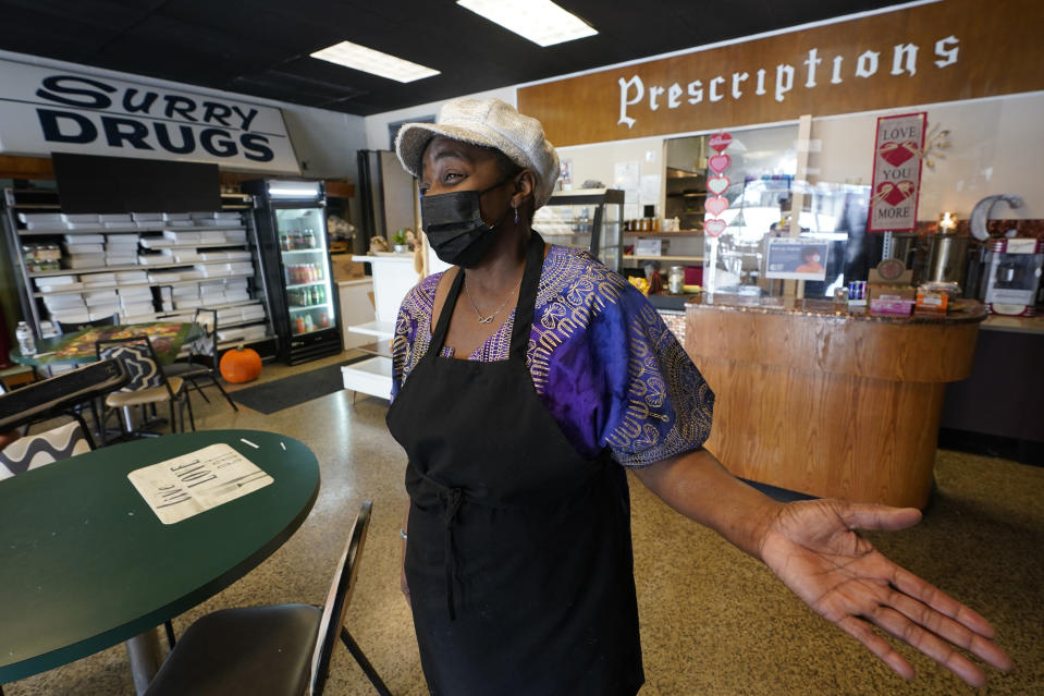 Co-owner of Creative Works Gallery and Cafe, Sarah Mayo, gestures during an interview in Surry, Va., Tuesday, Feb. 9, 2021. Mayo opened the cafe and gallery in an old pharmacy which closed. Mayo kept the pharmacy signs to remind people of what was there. (AP Photo/Steve Helber)