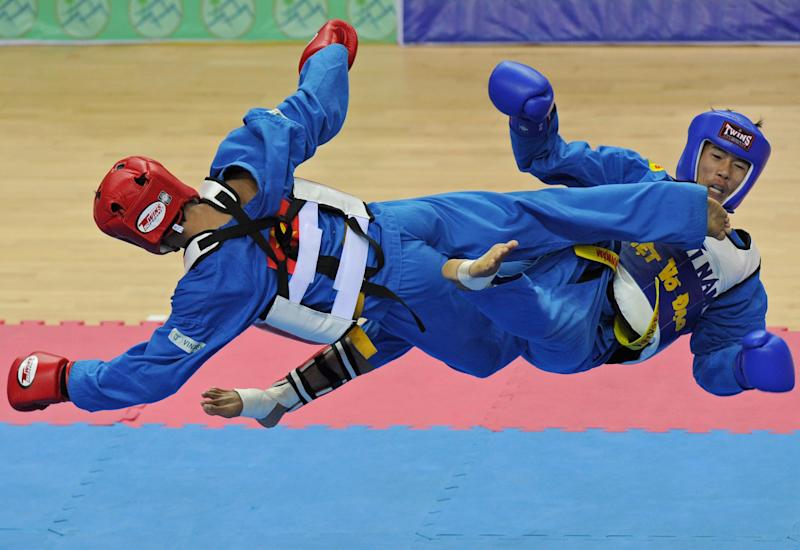Soukanh Taypanyavong (R) of Laos competes against Tran Anh Tuan (L) of Vietnam during the men's vovinam final 55 kg final at Zeyar Thiri stadium during the 27th Southeast Asian SEA Games in Naypyidaw on December 20, 2013. Nguyen Soukanh Taypanyavong won the gold medal. AFP PHOTO / SOE THAN WIN (Photo credit should read Soe Than WIN/AFP via Getty Images)