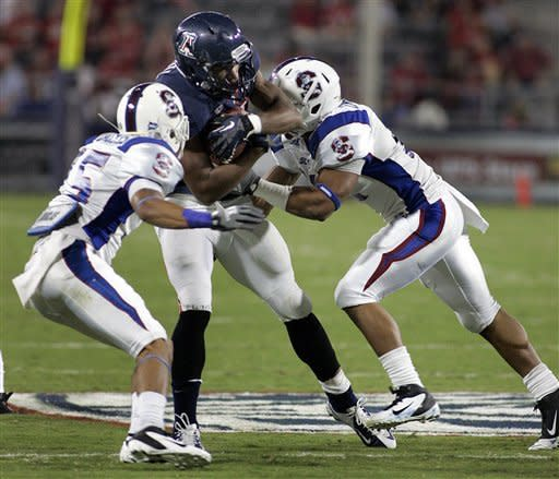 Arizona's Austin Hill, center, is dragged down by South Carolina State's Mason Harris (15) and Courtney Ingram (11) during the first half of an NCAA college football game at Arizona Stadium in Tucson, Ariz., Saturday, Sept. 15, 2012. (AP Photo/John Miller)