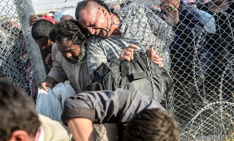 Syrians fleeing the war pass through border fences near the Turkish border crossing at Akcakale in Sanliurfa province on June 14, 2015 (AFP Photo/Bulent Kilic)