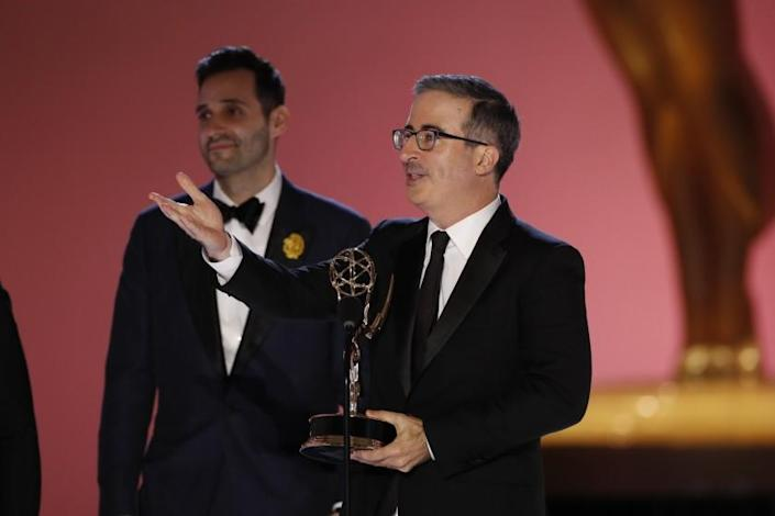 A man holding an Emmys trophy while speaking into a microphone and gesturing with his arm outstretched