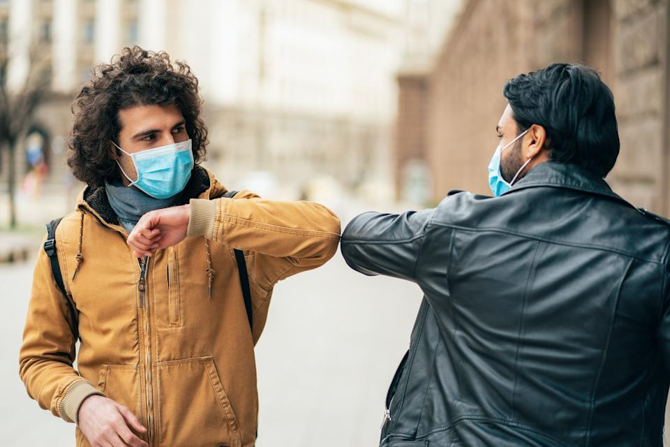 Young people friends meeting in quarantine and greeting without touching their hands (Photo: filadendron via Getty Images)