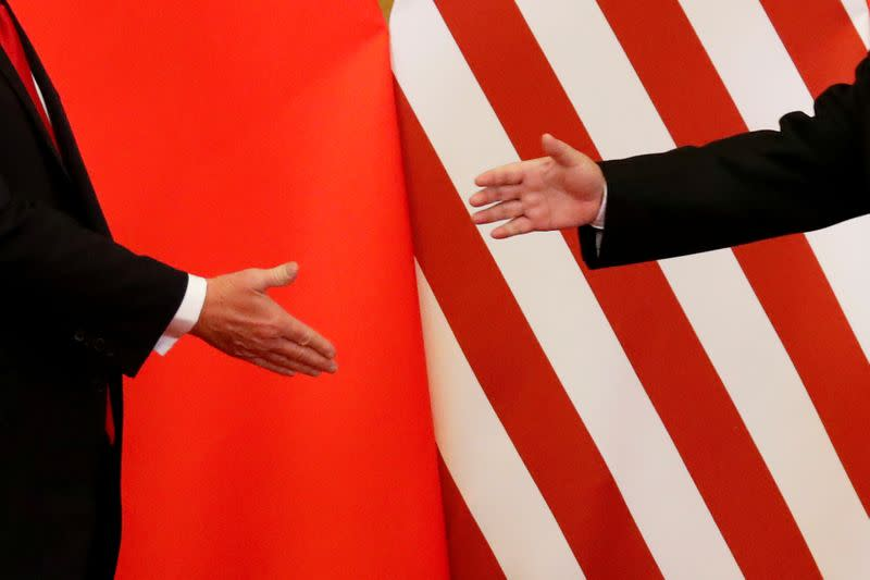 FILE PHOTO: U.S. President Donald Trump and China's President Xi Jinping shakes hands after making joint statements at the Great Hall of the People in Beijing