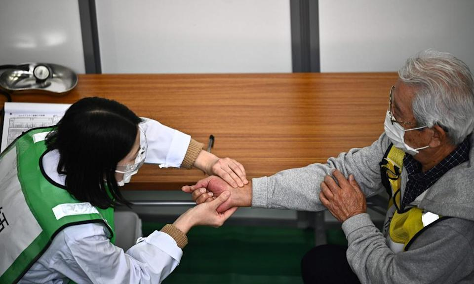 A doctor inspects a man participating in a Covid vaccination drill at the Kawasaki City College of Nursing