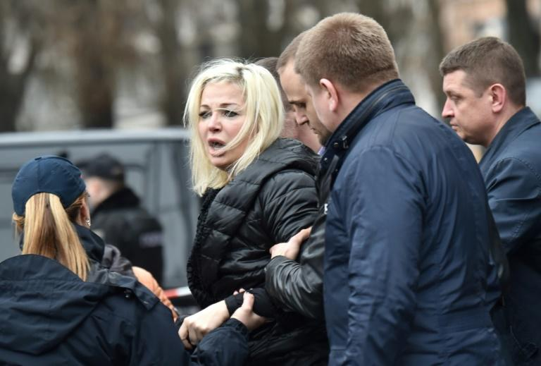 Policemen hold Maria Maksakova, wife of Denis Voronenkov, as she reacts near his body in the center of Kiev on March 23, 2017