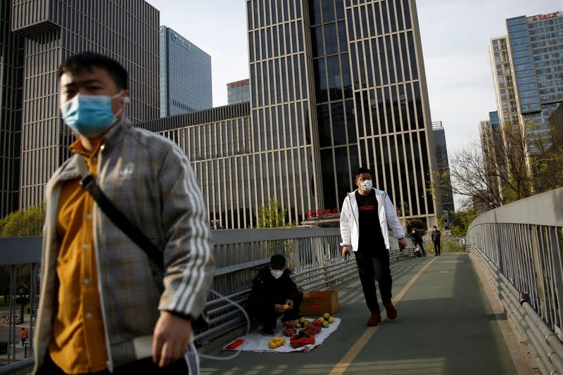 People wearing face masks walk on an overpass in Beijing's central business area, amid an outbreak of the novel coronavirus disease (COVID-19) in the country