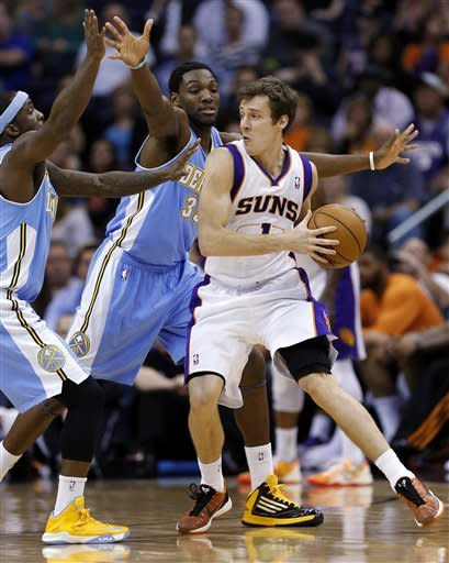 Phoenix Suns' Goran Dragic (1), of Slovenia, looks to pass around Denver Nuggets' Kenneth Faried (35) and Corey Brewer during the first half of an NBA basketball game, Monday, March 11, 2013, in Phoenix. (AP Photo/Matt York)