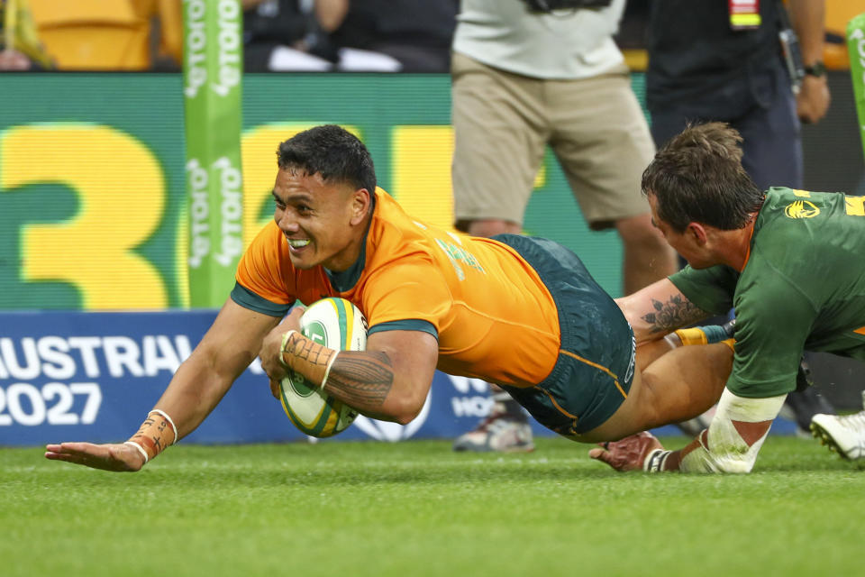 Australia's Len Ikitau, left, scores a try as South Africa's Franco Mostert attempts a tackle during the Rugby Championship test match between the Springboks and the Wallabies in Brisbane, Australia, Saturday, Sept. 18, 2021. (AP Photo/Tertius Pickard)