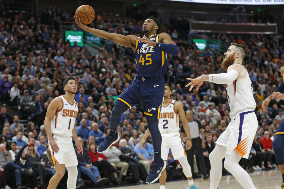 Utah Jazz guard Donovan Mitchell (45) goes to the basket as Phoenix Suns' Devin Booker (1) and Aron Baynes, right, watch in the first half during an NBA basketball game Monday, Feb. 24, 2020, in Salt Lake City. (AP Photo/Rick Bowmer)