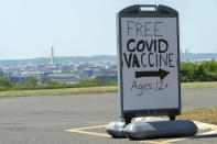 FILE - In this Wednesday, May 19, 2021 file photo, downtown Washington and the Washington Monument are seen behind a sign adverting a free vaccine drive with Pfizer COVID-19 vaccinations for members of the community 12 years and up outside a school in southeast Washington. On Friday, July 16, 2021, The Associated Press reported on stories circulating online incorrectly asserting President Joe Biden's administration introduced a door-to-door campaign to offer COVID-19 vaccines as a way to confiscate guns or Bibles. But the vaccine campaign does not involve federal workers, it relies on local officials, private sector workers and volunteers to go into areas where there are lower vaccination rates and provide information on where to access the vaccine. (AP Photo/Jacquelyn Martin, File)