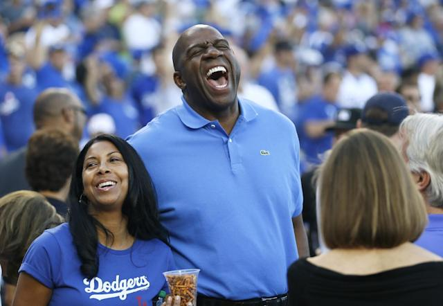 "Los Angeles Dodgers owner Earvin ""Magic"" Johnson, center, laughs as he attends Game 3 of the National League division baseball series between the Los Angeles Dodgers and the Atlanta Braves, Sunday, Oct. 6, 2013, in Los Angeles. (AP Photo/Danny Moloshok)"