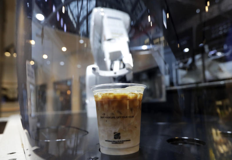 In this May 22, 2019, photo, a cup of coffee is placed by a robot named b:eat for a customer at a cafe in Seoul, South Korea. South Korea expands adoption of unmanned technology in businesses to meet the changing patterns of consumers who increasingly favor shopping or enjoying services with minimized human interactions and to reduce burdens of high labor costs. (AP Photo/Lee Jin-man)