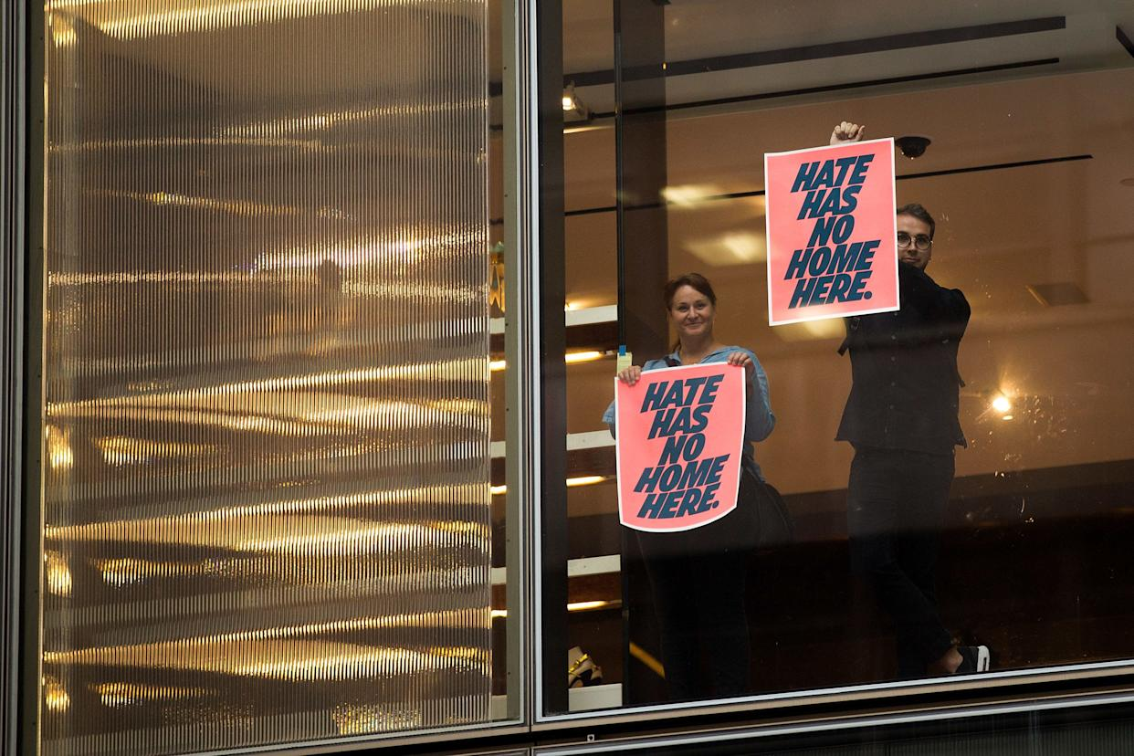 Supporters of anti-Trump protestors hold up signs inside Trump Tower ahead of President Donald Trump's arrival, August 14, 2017 in New York City.