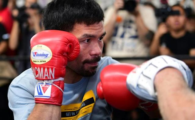 Eight-division world champion boxer Manny Pacquiao spars with his coach (AFP Photo/Frederic J. BROWN)