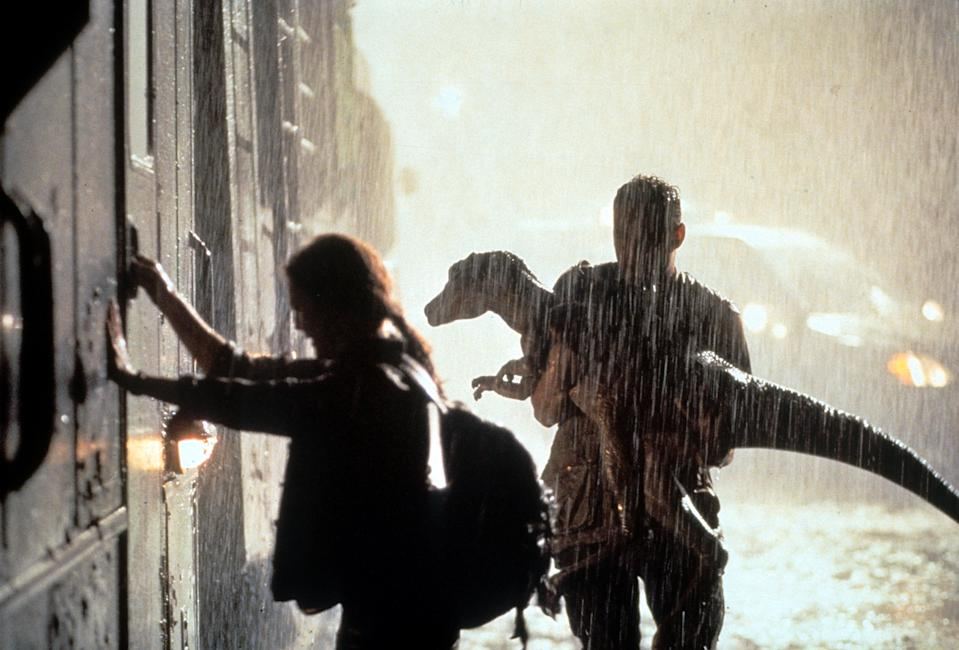 Julianne Moore grabbing the door of a train as Vince Vaughn holds a small dinosaur in a scene from the film 'The Lost World: Jurassic Park', 1997. (Photo by Universal Pictures/Getty Images)
