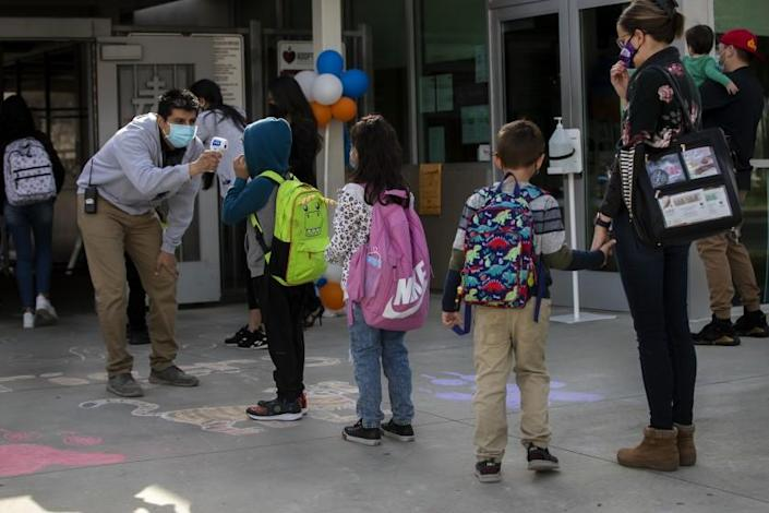 RIVERSIDE, CA - MARCH 9, 2021: Kindergarteners get their temperatures checked on the first day back to school at Pachappa Elementary on March 9, 2021 in Riverside, California. The K-6 school was closed on March 13, 2020 because of the coronavirus pandemic.The students have been divided into two groups. One group attends in-person learning on Tuesdays and the other on Thursdays. All students will stay in remote learning the other days of the week.(Gina Ferazzi / Los Angeles Times)