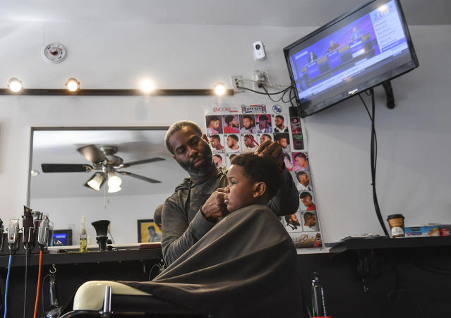 <p>Barber William Moore gives 4-year-old DJ Alexander a haircut at the Hands On Barber Shop in Mount Rainier, Md. </p>