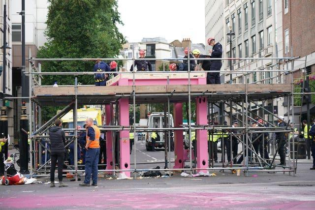Workers remove a large pink structure Extinction Rebellion activists erected to block a junction in London