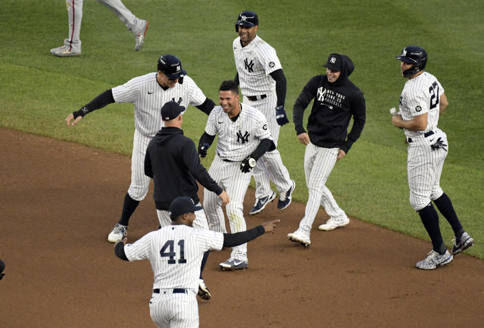 New York Yankees' Gleyber Torres, center, is congratulated by teammates after he drove in the winning run in the 11th inning of a baseball game to defeat the Washington Nationals 4-3, Saturday, May 8, 2021, at Yankee Stadium in New York. (AP Photo/Bill Kostroun)