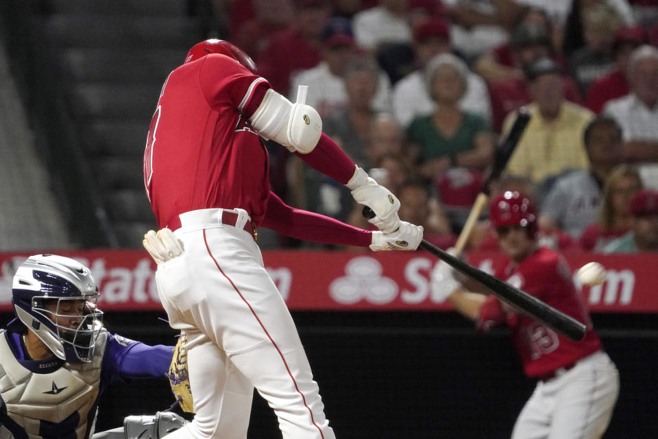 Los Angeles Angels' Shohei Ohtani, right, hits a two-run home run as Colorado Rockies catcher Elias Diaz watches during the sixth inning of a baseball game against the Colorado Rockies Tuesday, July 27, 2021, in Anaheim, Calif. (AP Photo/Mark J. Terrill)