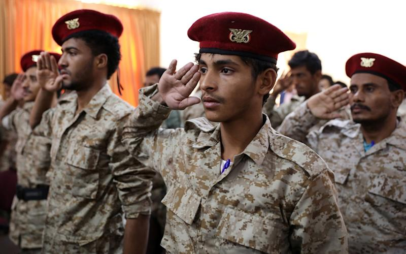 Soldiers who have defected from the ranks of Yemeni government forces salute for the national anthem during a ceremony held by the Houthis in Sanaa - REUTERS