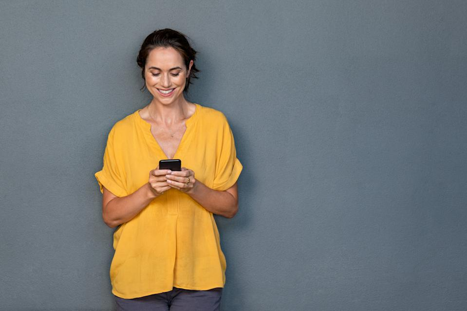 Smiling mature woman using smartphone isolated on gray wall with copy space. Happy latin woman in casual typing on cellphone over grey background. Portrait of cheerful middle aged lady messaging with smartphone.