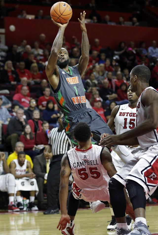 Florida A&M guard Willie Conner (1) knocks over Rutgers guard D'Von Campbell (55) as he takes a shot during the first half of an NCAA college basketball game in Piscataway, N.J., Friday, Nov. 8, 2013. (AP Photo/Mel Evans)