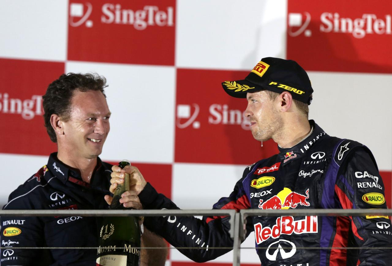 Red Bull team principal Christian Horner (L) celebrates on the podium with Red Bull Formula One driver Sebastian Vettel of Germany after Vettel won the Singapore F1 Grand Prix at the Marina Bay street circuit in Singapore September 22, 2013. Vettel cruised to a third straight Singapore Grand Prix victory on Sunday and moved closer to a fourth consecutive Formula One world title with a dominant drive under the floodlights at the Marina Bay Street Circuit. REUTERS/Pablo Sanchez (SINGAPORE - Tags: SPORT MOTORSPORT F1)