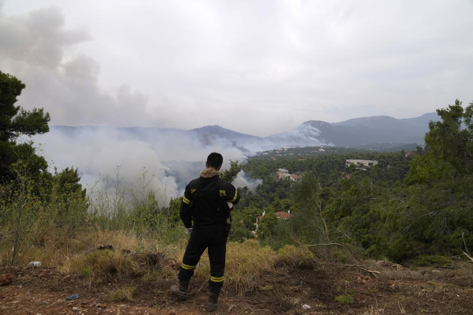 Wildfire burns a forest as firefighter stands on a mountain in Ippokratios Politia village, about 35 kilometres (21 miles) north of Athens, Greece, Friday, Aug. 6, 2021. Thousands of residents of the Greek capital have fled to safety from a wildfire that burned for a fourth day north of Athens as crews battle to stop the flames reaching populated areas, electricity installations and historic sites. (AP Photo/Thanassis Stavrakis)