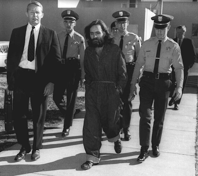 <p>Charles Manson is escorted by officers en route to court in Independence, Calif., on Dec. 3, 1970. Manson and three women co-defendants were convicted and sentenced to death after the 10-month trial that involved the murders of actress Sharon Tate and six others in the hills near Hollywood, Calif. Their sentences were later commuted to life when the death penalty was briefly outlawed. (Photo: AP) </p>
