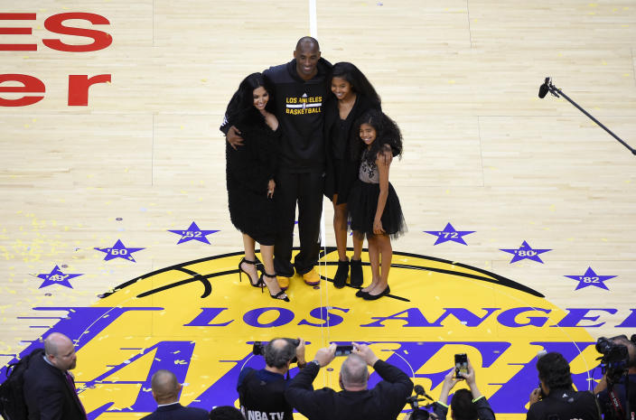 FILE - In this April 13, 2016, file photo, Los Angeles Lakers' Kobe Bryant poses for pictures with his wife Vanessa, left, and daughters Natalia, second from right, and Gianna as they stand on the court after an NBA basketball game against the Utah Jazz, in Los Angeles. Kobe Bryant's legacy may be stronger than ever. Tuesday, Jan. 26, 2021, marks the anniversary of the crash that took the lives of Bryant, Gianna and seven other people. (AP Photo/Mark J. Terrill, File)