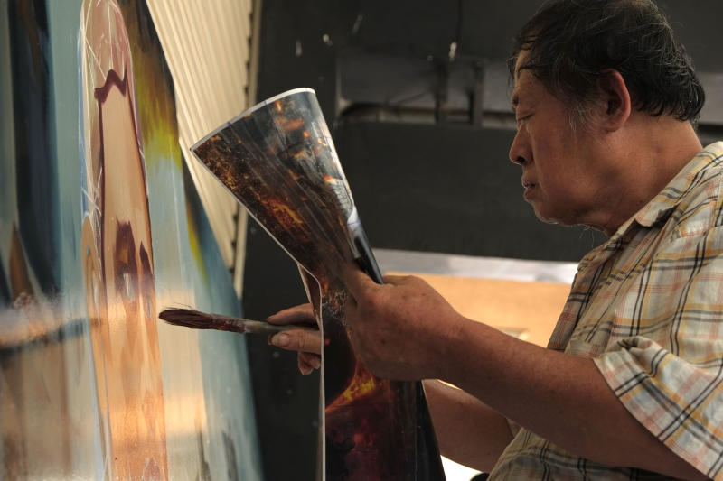 In this Friday, Sept. 6, 2013 photo, local artist Yan Jhen-fa paints a movie poster at his makeshift sidewalk studio for the Chuan Mei Theater in Tainan, Taiwan. The Chuan Mei's main attraction is the colorful 3-meter (9-foot) -square oil-painted advertising posters hung above the theater entrance to illustrate the daily bill of fare. They are the life work of 61-year-old Yan, the last practitioner of this once-popular art form in the country. (AP Photo/Wally Santana)