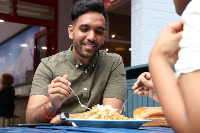 A mid-shot of a man smiling as he sits at an outdoor table eating food from a plate.
