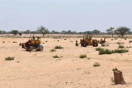 Bulldozers prepare a field for construction on what is slated to be Senegal's largest solar plant in Santhiou Mekhe