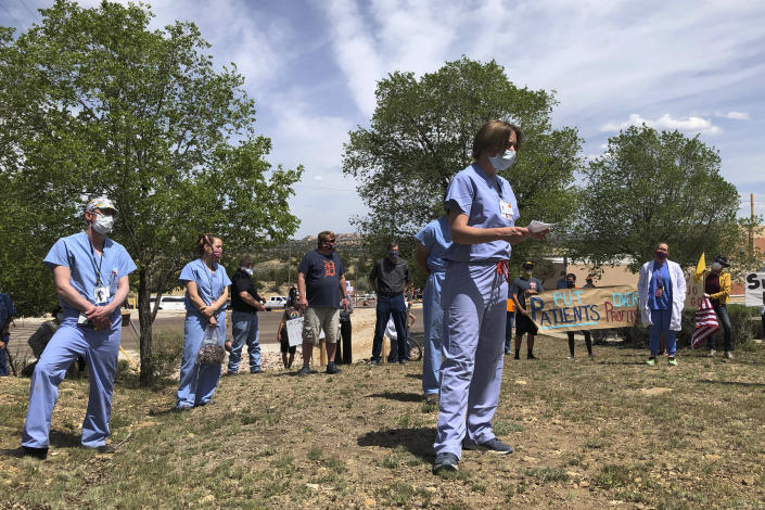 In this photo taken May 8, 2020, medical staff from Rehoboth McKinley Christian Hospital including Chief Medical Officer Val Wangler, center, hold a protest over working conditions and depleted staff in Gallup, N.M. Many nurses and doctors say staffing at the hospital was inadequate because of hospital CEO David Conejo's move to cut back on nurses in the first week of March to offset declining hospital revenues after elective surgeries were suspended. They voiced their discontent at the recent protest calling for his resignation. (AP Photo/Morgan Lee)