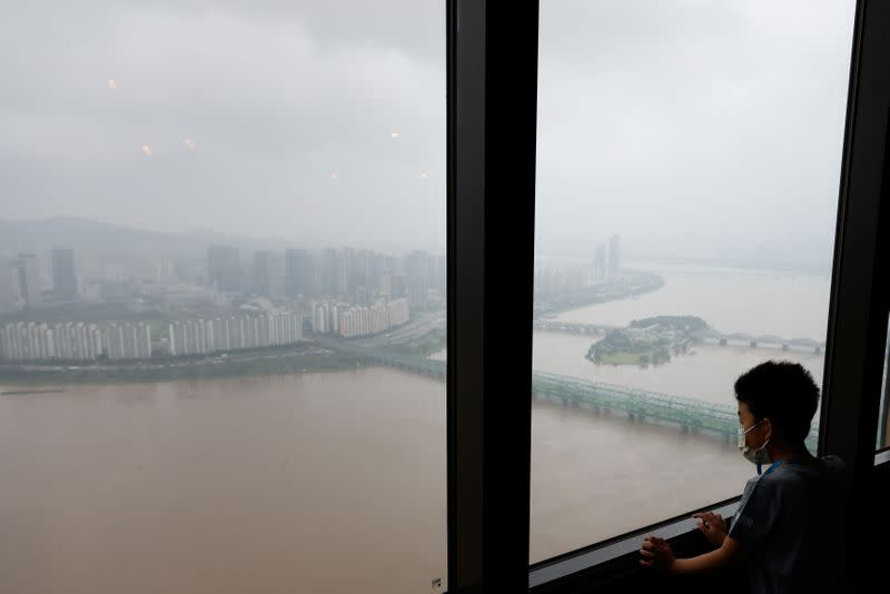 Boy looks down at a flooded Han River park from an observatory platform in Seoul