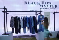 A woman takes pictures of fashion designer Sheetal's creations, as part of the Black Lives Matter Spring Summer 2022 collective fashion event, unveiled during the Milan Fashion Week, in Milan, Italy, Tuesday, Sept. 21, 2021. (AP Photo/Antonio Calanni)