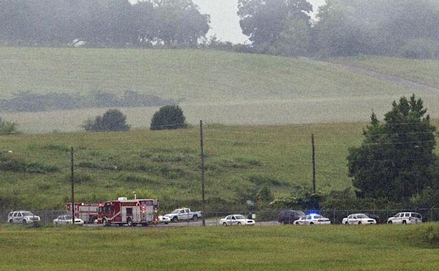 Fire crews arrive on scene of a plane crash at the Birmingham International Airport in Birmingham, Ala., on Wednesday, Aug. 14, 2013. An airport spokeswoman says the large UPS cargo plane that crashed went down in an open field just outside the airport. (AP Photo/Butch Dill)